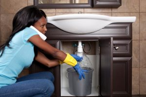 woman-with-bucket-under-sink